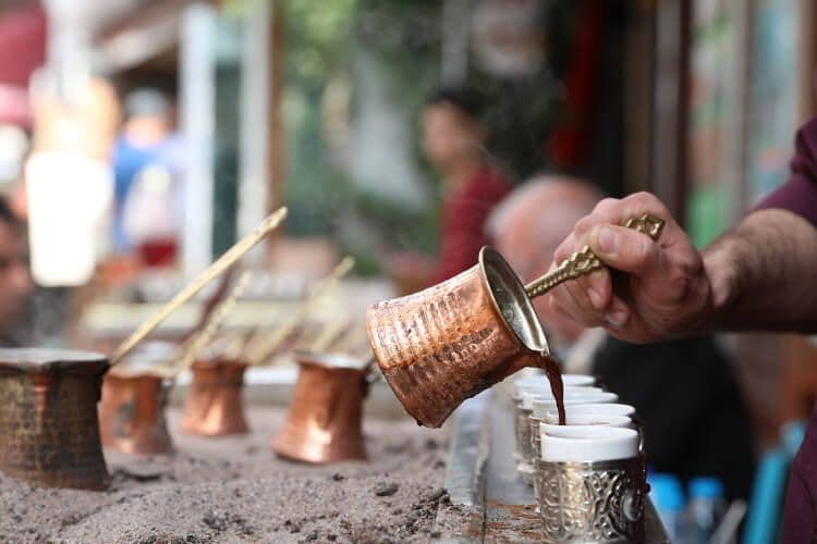 A hand pouring Turkish coffee into white cups from sand.