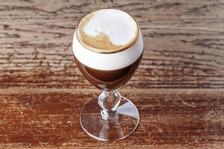 A lgith brown coffee with generous foam in a fluted clear glass on a brown table in Austria.