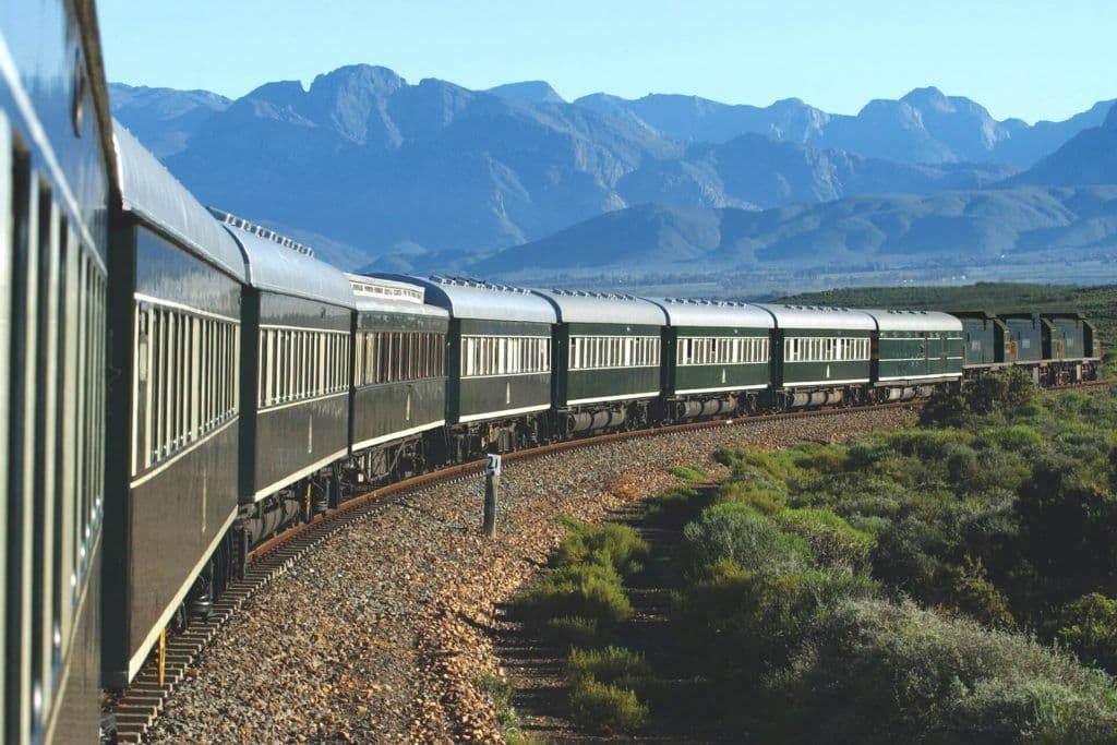The Rovos Rail in South Africa with mountains in the background.