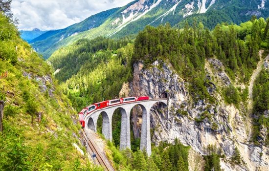 The Glacier Express travelling on a bridge in Switzerland